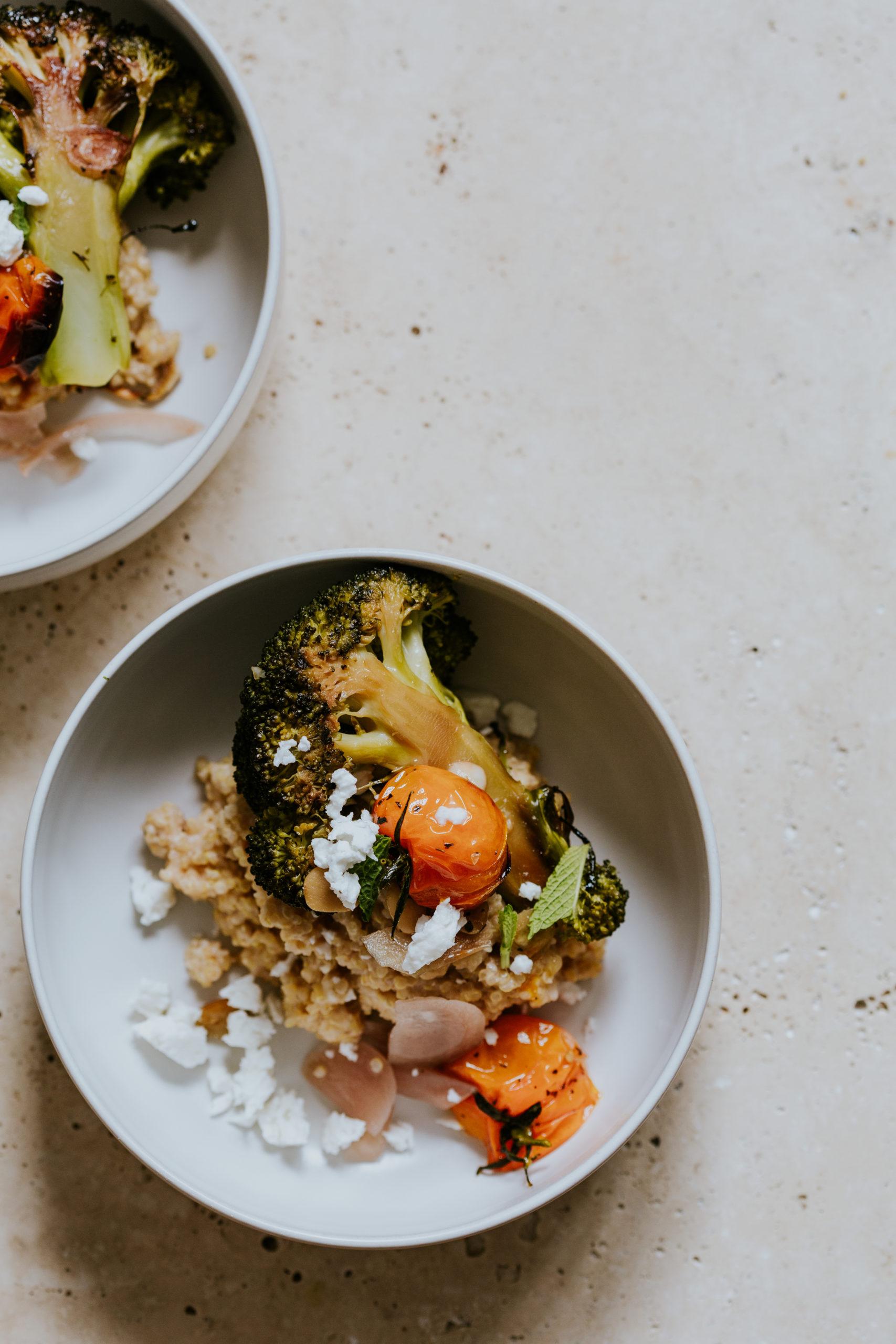 Porridge de quinoa à la feta et tomates rôties avec brocoli rôti et mijoté avec de l'ail bien doré, sauce menthe coriandre, pickles d'oignons.